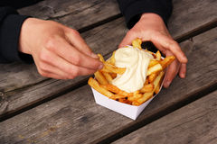 Belgian pommes frites. Hands with a tray of Belgian fries and mayonnaise on top Stock Photography