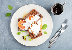 Belgian soft waffles with blood orange, cream, marple syrup and mint  on white plates Royalty Free Stock Photography