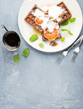 Belgian soft waffles with blood orange, cream, marple syrup and mint on white plates Stock Photo