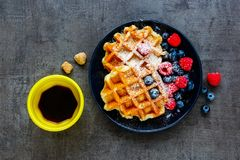 Belgian soft waffles. Breakfast set flat-lay. Homemade Belgian soft waffles with berry on black plate, espresso cup and cubes of brown sugar over dark vintage Royalty Free Stock Image