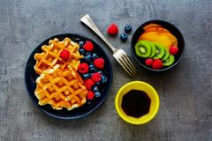 Belgian soft waffles. Breakfast set flat lay. Homemade Belgian soft waffles with berry on black plate, fresh fruit, cup of espresso and cubes of brown sugar over Stock Images