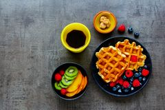 Belgian soft waffles. Tasty breakfast set. Homemade Belgian soft waffles with berry on black plate, fresh t, cup of espresso and cubes of brown sugar over dark Stock Images