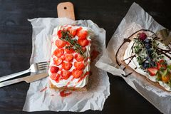 Belgian waffels with fresh berries and whipped cream on cutting board in rustic style on black table.Breakfast concept royalty free stock image