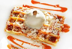 Belgian waffle with  ball of vanilla ice cream. Caramel syrup and almonds Stock Image