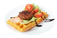 Belgian waffle with beefsteak, tomato slices, lettuce leaf and sauce. Royalty Free Stock Photo