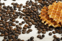 Belgian Waffle biscuit and coffee beans scattered on light surface Royalty Free Stock Images