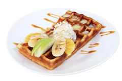 Belgian waffle with condensed milk, whipped cream and fruit. Dessert dish, Belgian waffle with condensed milk, whipped cream and slices of fruit, banana, apple stock photography