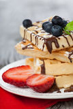 Belgian waffle. Delicious Belgian waffle with fresh berries and chocolate for breakfast Royalty Free Stock Photography