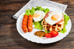 Belgian waffle with egg and sausage on wood table Stock Images