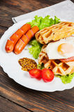 Belgian waffle with egg and sausage on wood table Royalty Free Stock Image