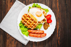 Belgian waffle with egg and sausage on wood table Stock Photo