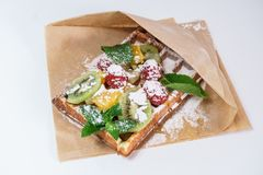 Belgian waffle with fruit and powdered sugar on a white background royalty free stock photos