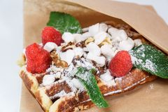 Belgian waffle with fruit and powdered sugar on a white background stock photo