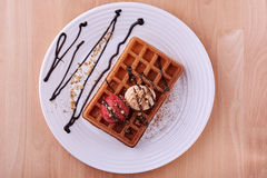 Belgian waffle with ice cream. Dessert on wooden background Stock Photos