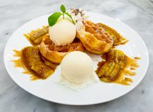 Belgian waffle with ice cream and grilled banana topped with honey. Stock Image