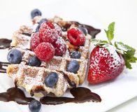 Belgian waffle with powdered sugar, chocolate syrup, and fruit o royalty free stock photography