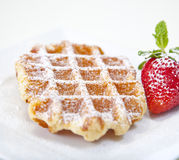 Belgian waffle with powedered sugar and a strawberry isolated on. Belgian waffle with powedered sugar and a strawberry Royalty Free Stock Images