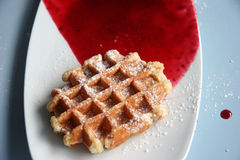 Belgian Waffle. A belgian waffle with sugar icing and red cherry sauce Royalty Free Stock Image