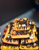 Belgian waffle topped with chocolate. Delicious Belgian waffle topped with chocolate on a dark background Stock Photos