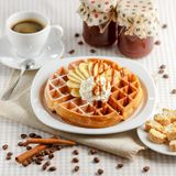 Belgian waffles with bananas and whipped cream. Decorated with caramel sauce and powdered sugar on the table with a cup of coffee, coffee beans with cinnamon Stock Image