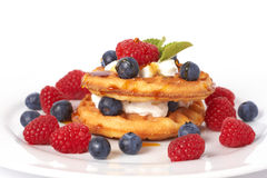 Belgian waffles with berries and cream. Belgian waffles with fresh raspberries, blueberries, mint leaves and cream on white plate Royalty Free Stock Photo