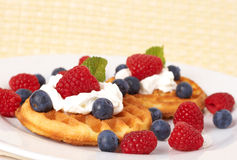 Belgian waffles with berries and cream. Belgian waffles with fresh raspberries, blueberries, mint leaves and cream on white plate Stock Images