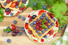Belgian waffles and berry fruit. Belgian waffles with fresh raspberries, grapes, blueberries and cream Stock Photos