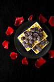 Belgian waffles with blackberries on a black background with petals of roses Stock Photos