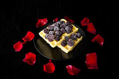 Belgian waffles with blackberries on a black background with petals of roses Royalty Free Stock Photos