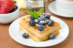 Belgian waffles with blueberries, coffee and fresh fruit Royalty Free Stock Photos