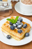 Belgian waffles with blueberries, coffee and fresh fruit Royalty Free Stock Image