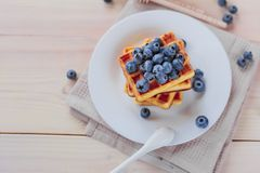 Belgian waffles with blueberries on the light wooden table. Healthy breakfast. Horizontal format. Top view. Copy text space Stock Photos