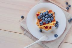 Belgian waffles with blueberries on the light wooden table. Healthy breakfast. Horizontal format. Top view. Copy text space Royalty Free Stock Image