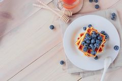 Belgian waffles with blueberries on the light wooden table. Healthy breakfast. Horizontal format. Top view. Copy text space Stock Images