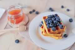 Belgian waffles with blueberries on the light wooden table. Healthy breakfast. Horizontal format. Top view. Copy text space Royalty Free Stock Images