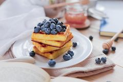 Belgian waffles with blueberries on the light wooden table. Healthy breakfast. Horizontal format Royalty Free Stock Photography