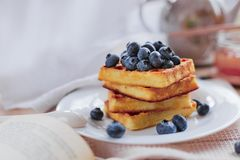 Belgian waffles with blueberries on the light wooden table. Healthy breakfast. Horizontal format Royalty Free Stock Photos
