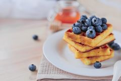 Belgian waffles with blueberries on the light wooden table. Healthy breakfast. Horizontal format Royalty Free Stock Images