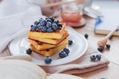 Belgian waffles with blueberries on the light wooden table. Healthy breakfast. Horizontal format. royalty free stock photography