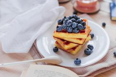 Belgian waffles with blueberries on the light wooden table. Healthy breakfast. Horizontal format Royalty Free Stock Image
