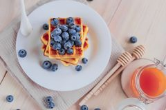 Belgian waffles with blueberries on the light wooden table. Healthy breakfast. Horizontal format Stock Images