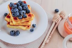 Belgian waffles with blueberries on the light wooden table. Healthy breakfast. Horizontal format Stock Photos