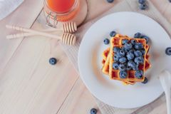 Belgian waffles with blueberries on the light wooden table. Healthy breakfast. Horizontal format. Top view. Copy text space Stock Photo
