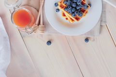 Belgian waffles with blueberries on the light wooden table. Healthy breakfast. Horizontal format. Top view. Copy text space Royalty Free Stock Photo