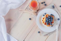 Belgian waffles with blueberries on the light wooden table. Healthy breakfast. Horizontal format. Top view. Copy text space Royalty Free Stock Photography