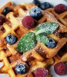 Belgian waffles with blueberries, raspberries and powdered sugar on wooden table. Belgian waffles with blueberries, raspberries  and powdered sugar on wooden Stock Photo