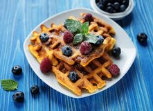 Belgian waffles with blueberries, raspberries and powdered sugar on wooden table. Belgian waffles with blueberries, raspberries  and powdered sugar on wooden Stock Photography