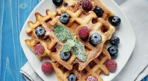 Belgian waffles with blueberries, raspberries and powdered sugar on wooden table. Belgian waffles with blueberries, raspberries  and powdered sugar on wooden Stock Image