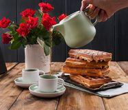 Belgian waffles for breakfast for two. Homemade pastries and a bouquet of red roses on the table. Delicious romantic lunch. Free. Belgian waffles for breakfast stock photos
