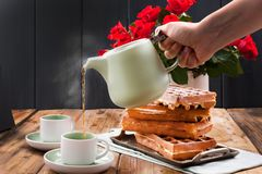 Belgian waffles for breakfast for two. Homemade pastries and a bouquet of red roses on the table. Delicious romantic lunch. Photo. Belgian waffles for breakfast stock photos